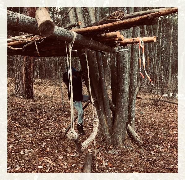 Bambino che gioca in una capanna nel bosco