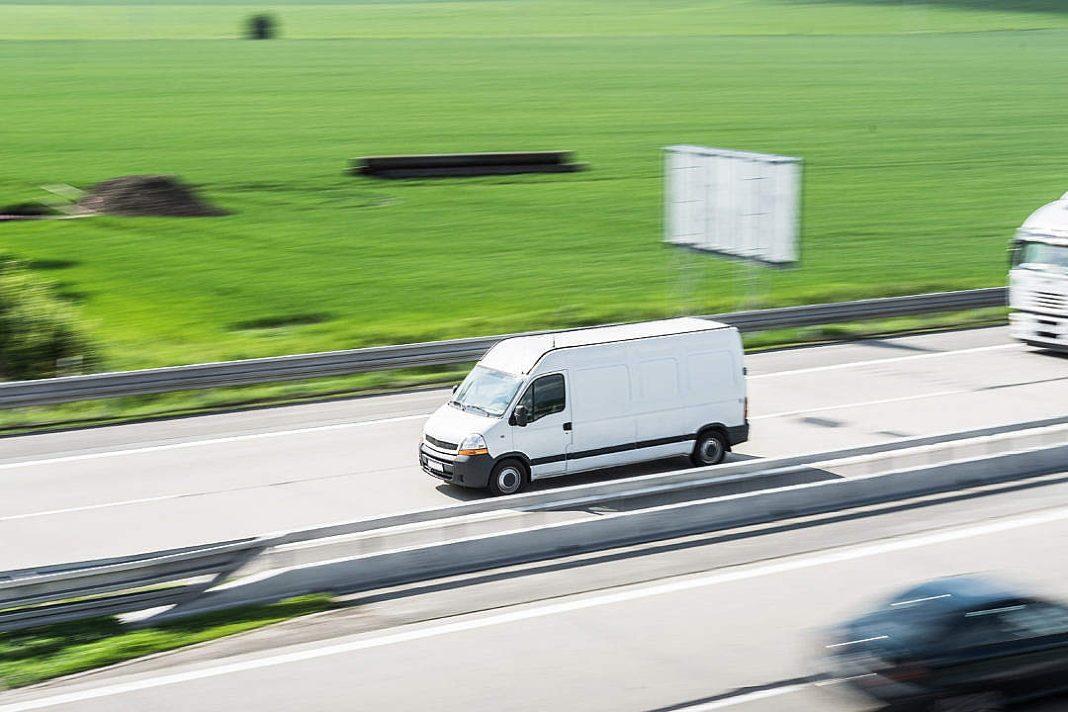 Corriere su furgone bianco in autostrada