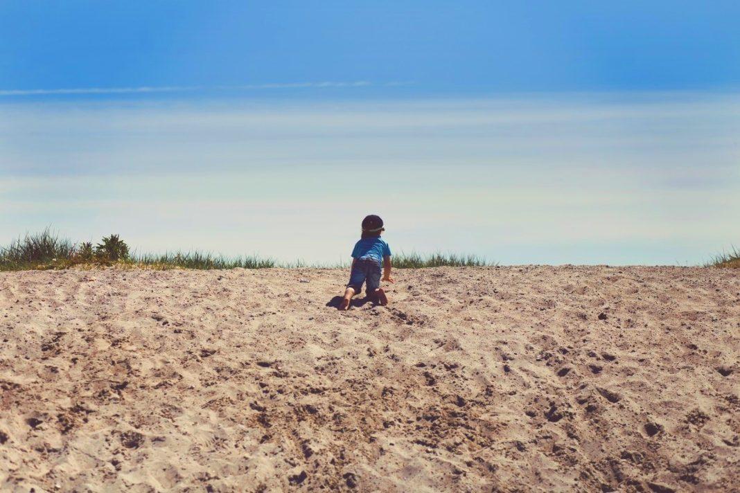 Bambino da solo alla scoperta nella sabbia: dove inizia l'educazione digitale dei bambini?