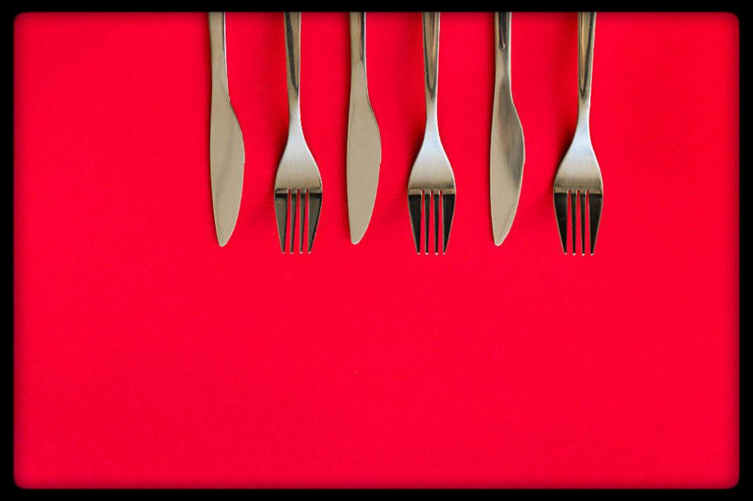 Posate su sfondo rosso: apparecchiare la tavola come primo passo per farsi aiutare in casa dai figli