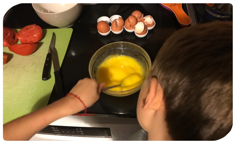 Bambino che sbatte le uova: iniziare dalla cucina per farsi aiutare dai figli in casa